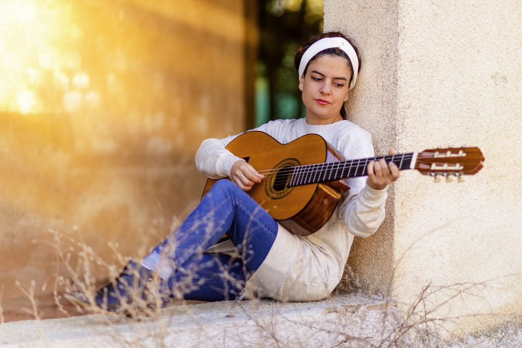 Girl plays guitar while leaning against a wall.