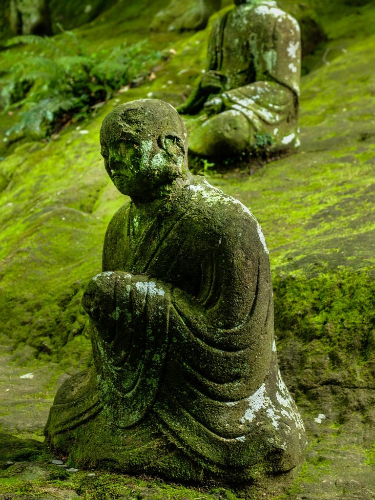 Buddha statue on a green hillside