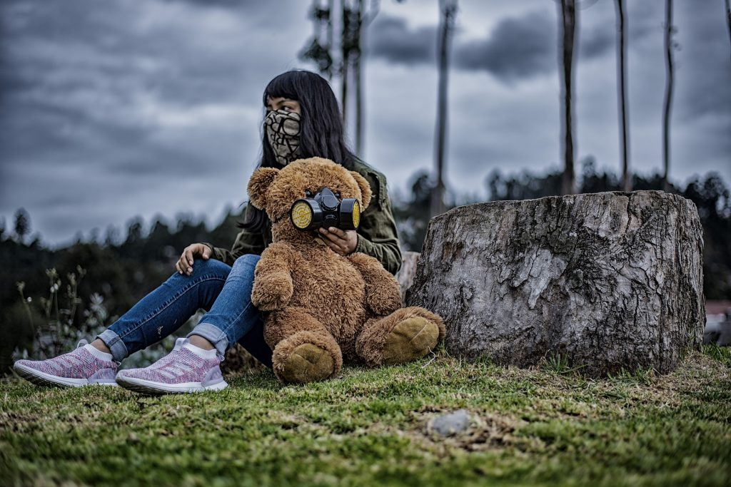 A young woman illustrates behavioral immunity by isolating herself frorm everyone but a teddy bear.