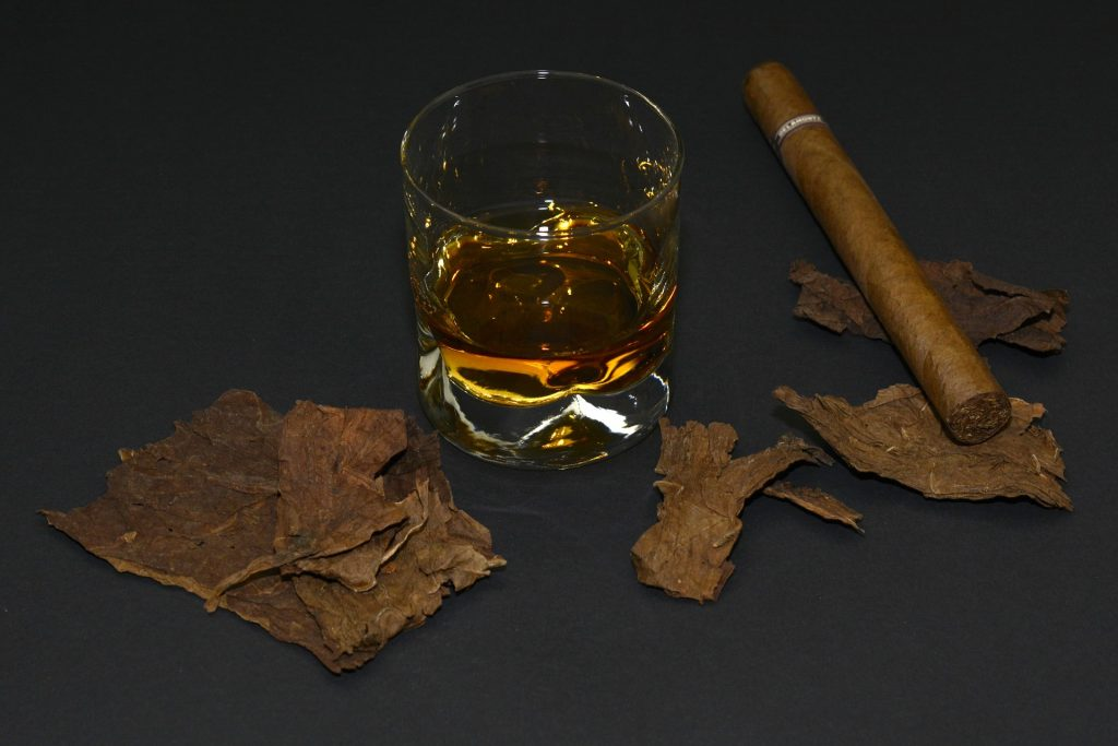 A glass of liquor and cigars beside it lie on a table.