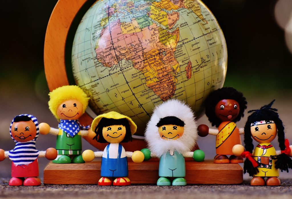 Dolls representing different cultures are displayed in front of a world globe.