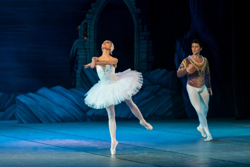 Ballet dancers are shown performing on stage.