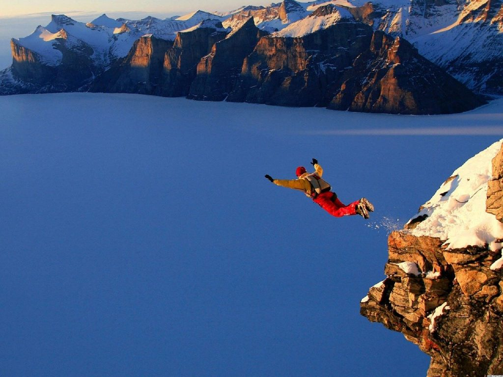 A BASE jumper is shown leaping off a cliff from a great height.