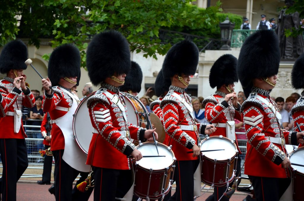 British palace guards are shwon marching with drums.