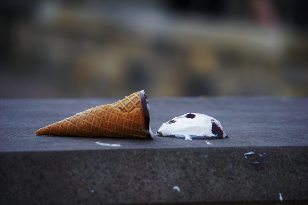 A dropped ice cream cone lies on the sidewalk.