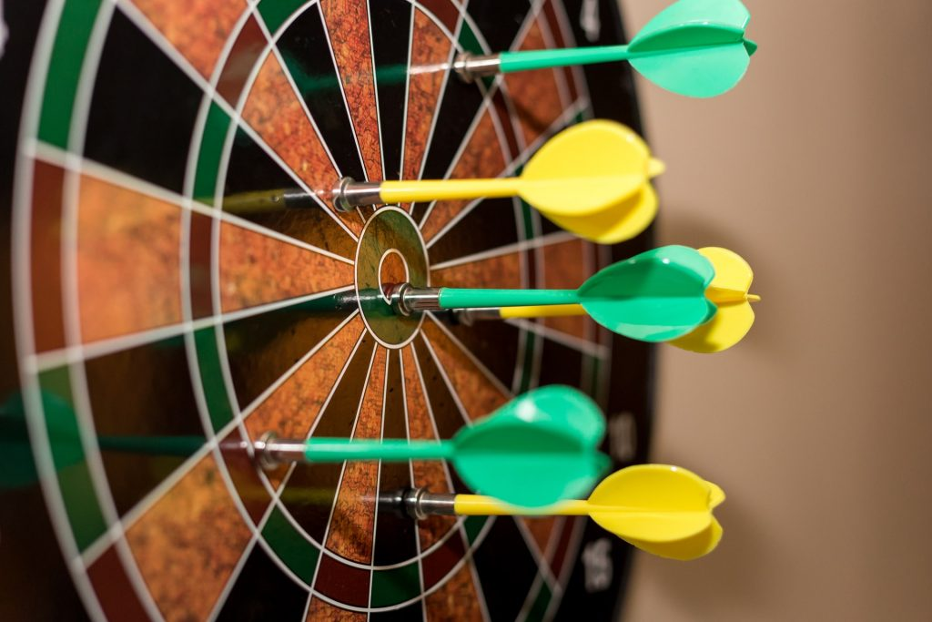 A number of darts have been thrown into a dartboard.
