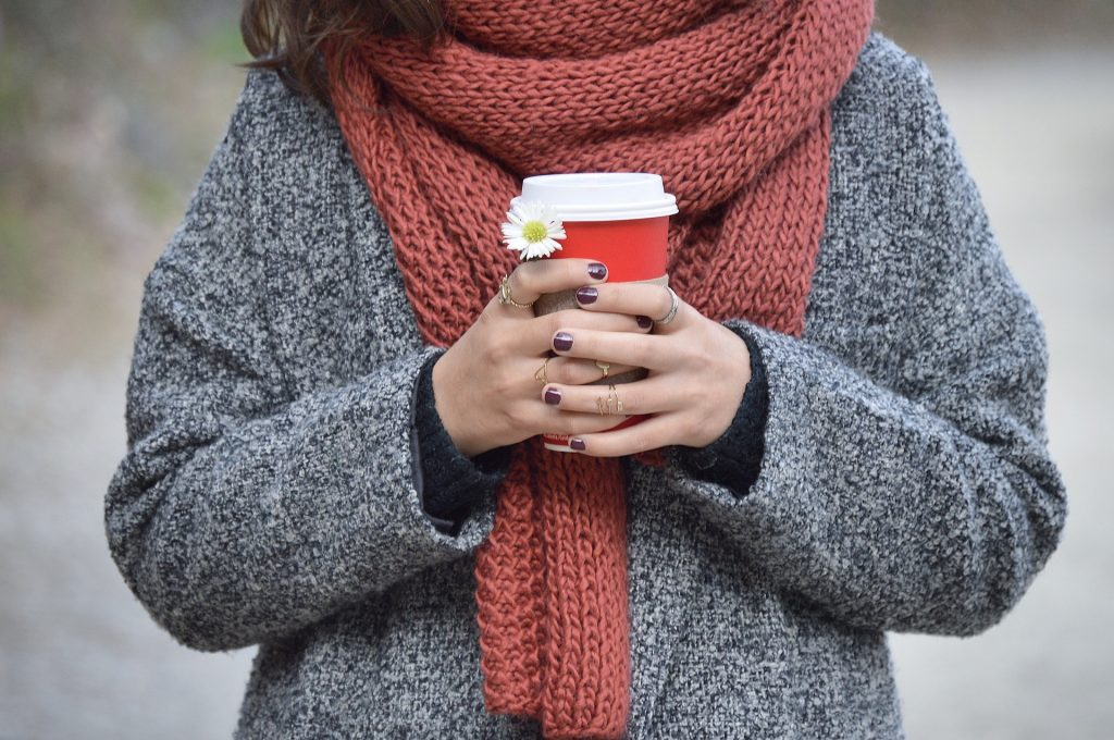 A woiman, bundled in coat and scarf, holds a cup of coffee.