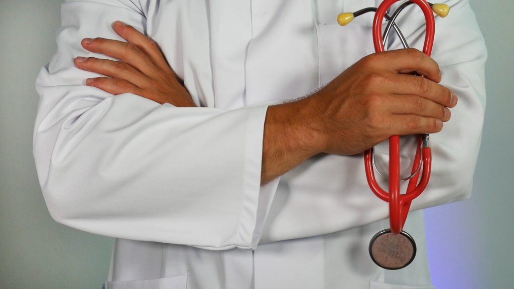 A medical professional in a white coat is shown with a stethoscope.