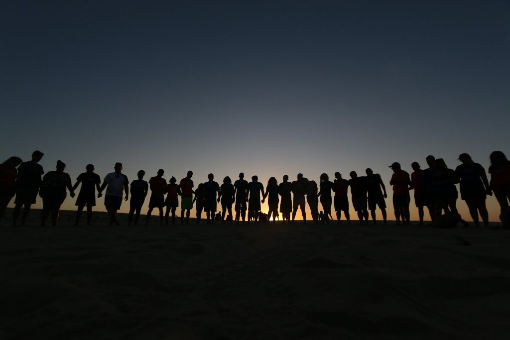A long line of people silhouetted against a setting sun