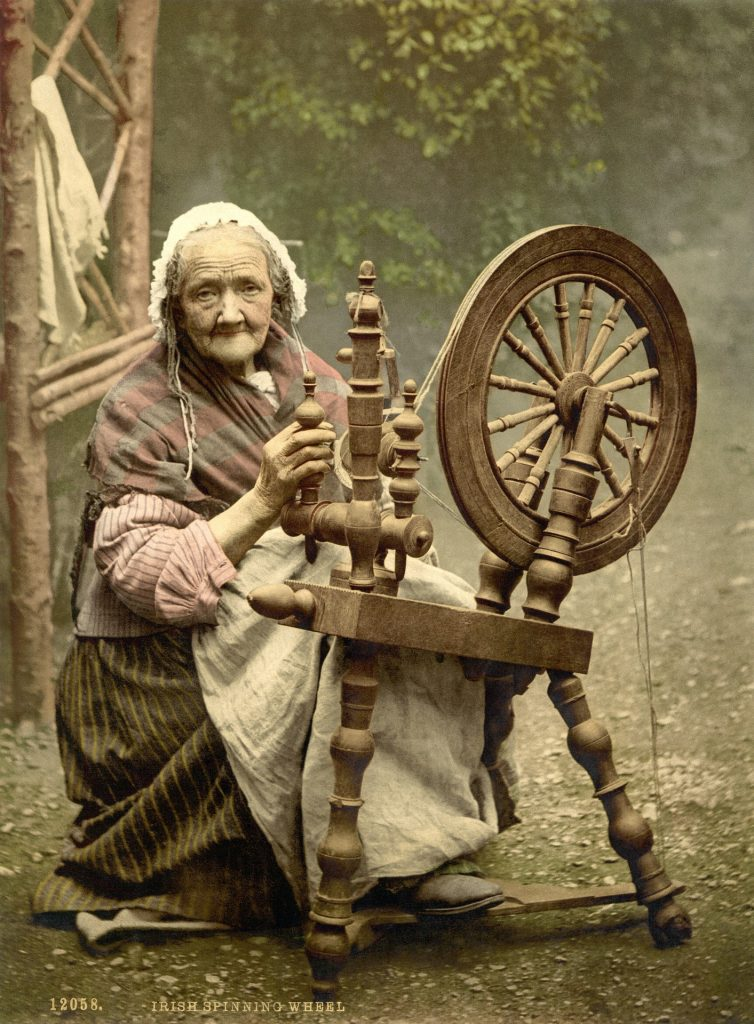 A woman is shown seated at a spinning wheel.