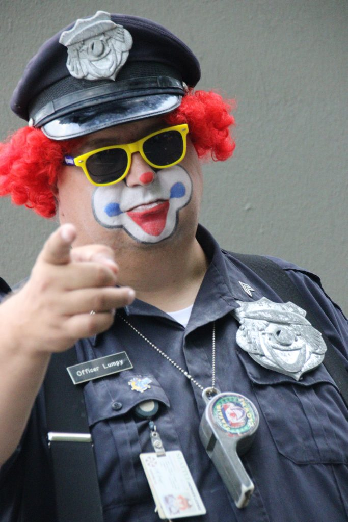 A police office in clown makeup is shown.