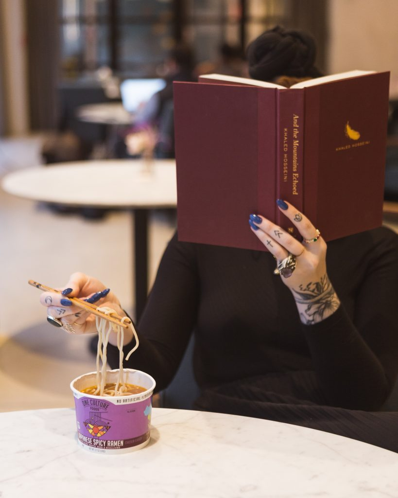 A woman sits at a table reading a book while using chopsticks to eat noodles.