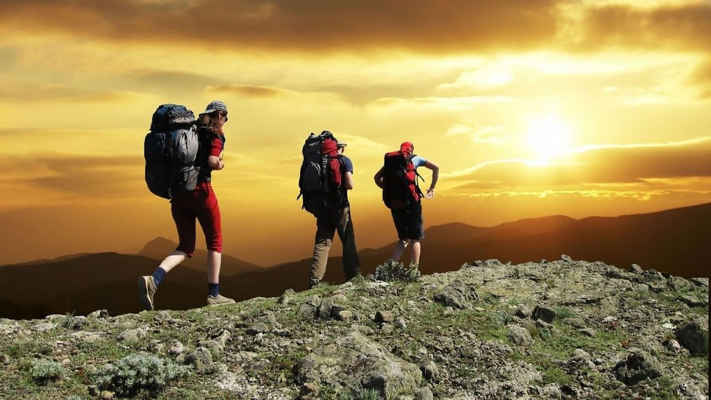 A trio of hikers are shown in the mountains at sunset.
