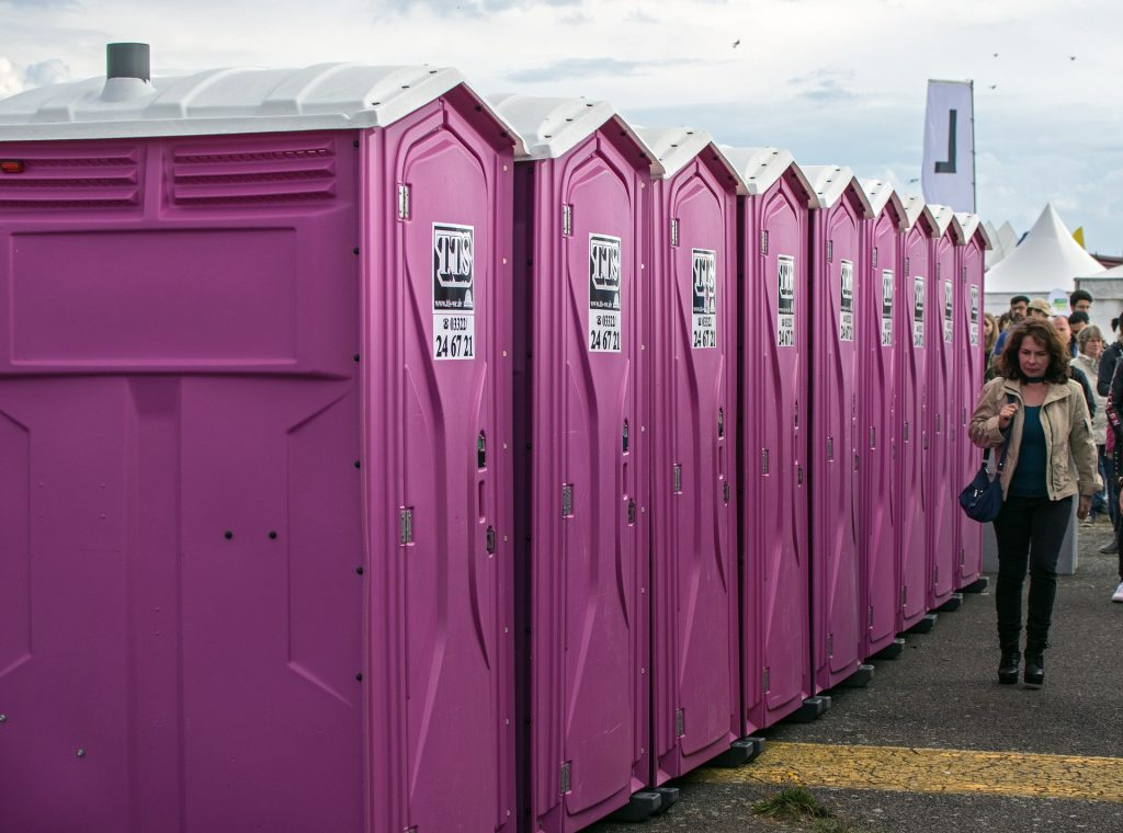 A woman waits outside a row of portable toilets.
