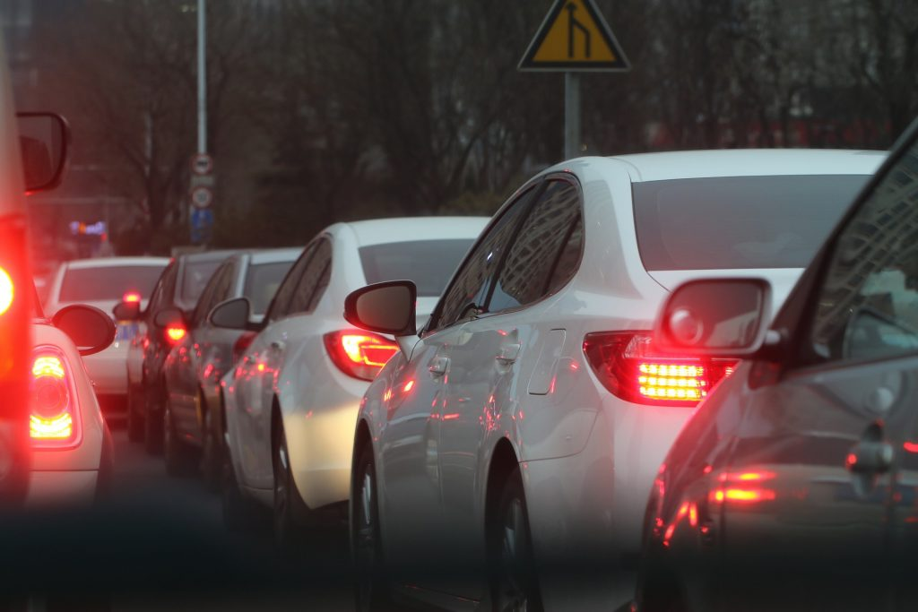 A traffic jam shows a line of cars with brake lights lit.