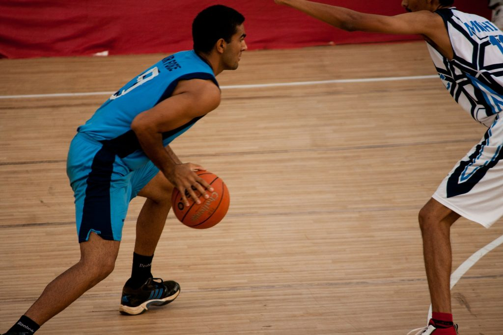 A basketball player is facing an opposing player.