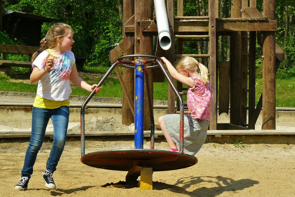 Two girls are shown playing in a playground.