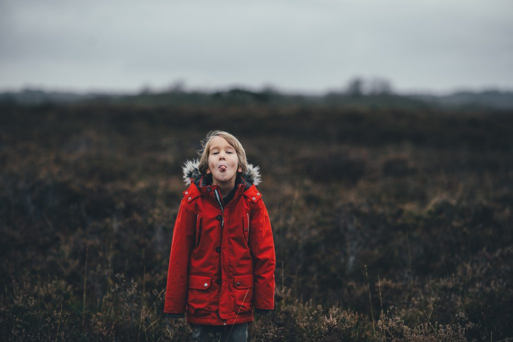 A child stands in a field with its tongue stuck out at the viewer.