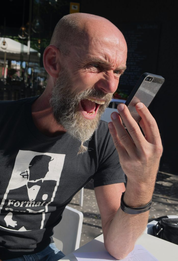 A middle-aged man in a t-shirt is frowning at a cell phone and appears to be yelling at it.