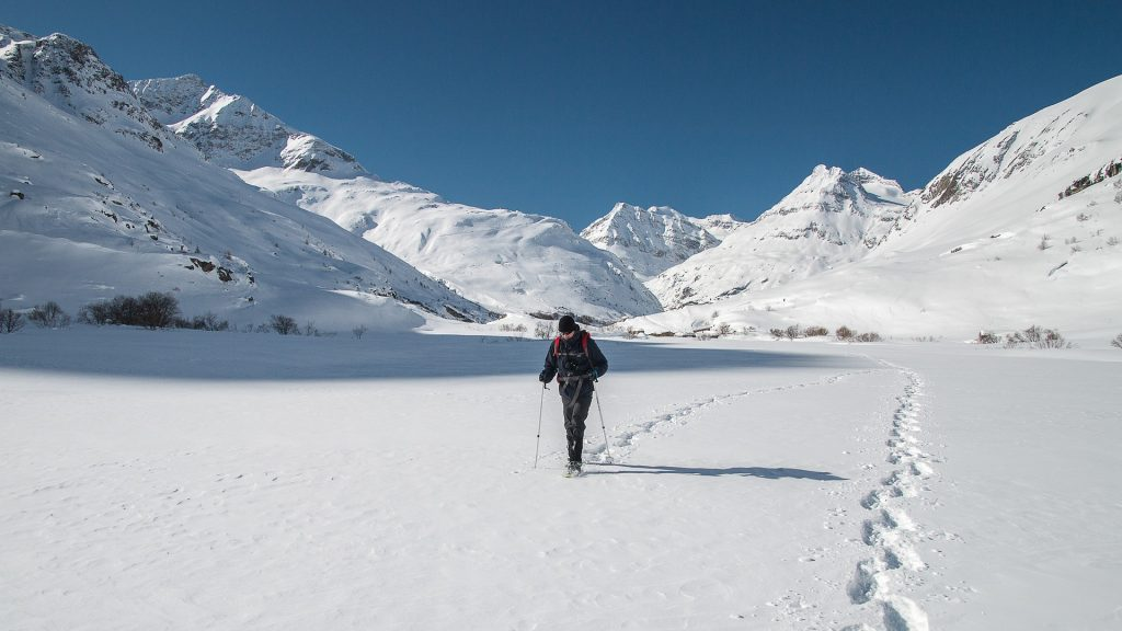 A lone figure traverses a snowy moutain valley.