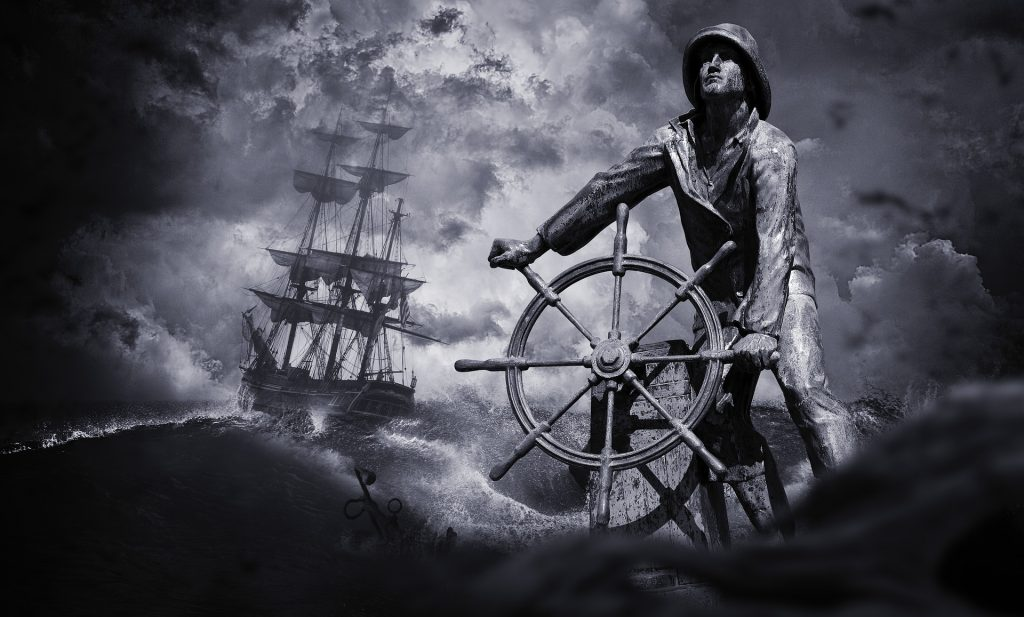 A sailor is shown at the wheel of his ship, against a background of a ship on a stormy sea.