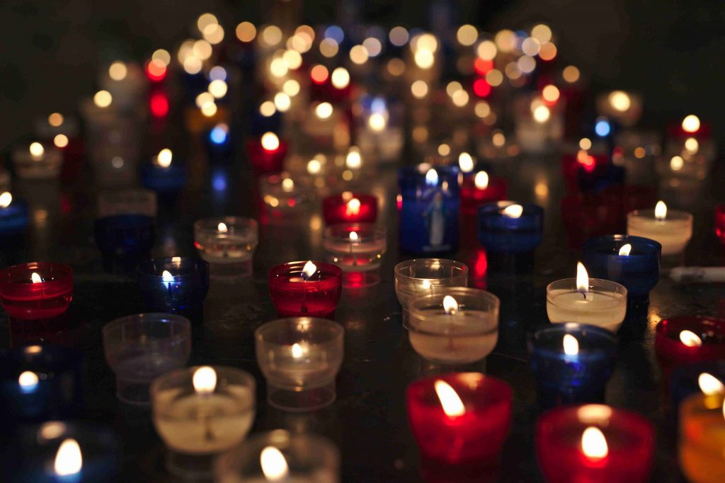 Dozens of flickering candles are shown, each with a small flame.