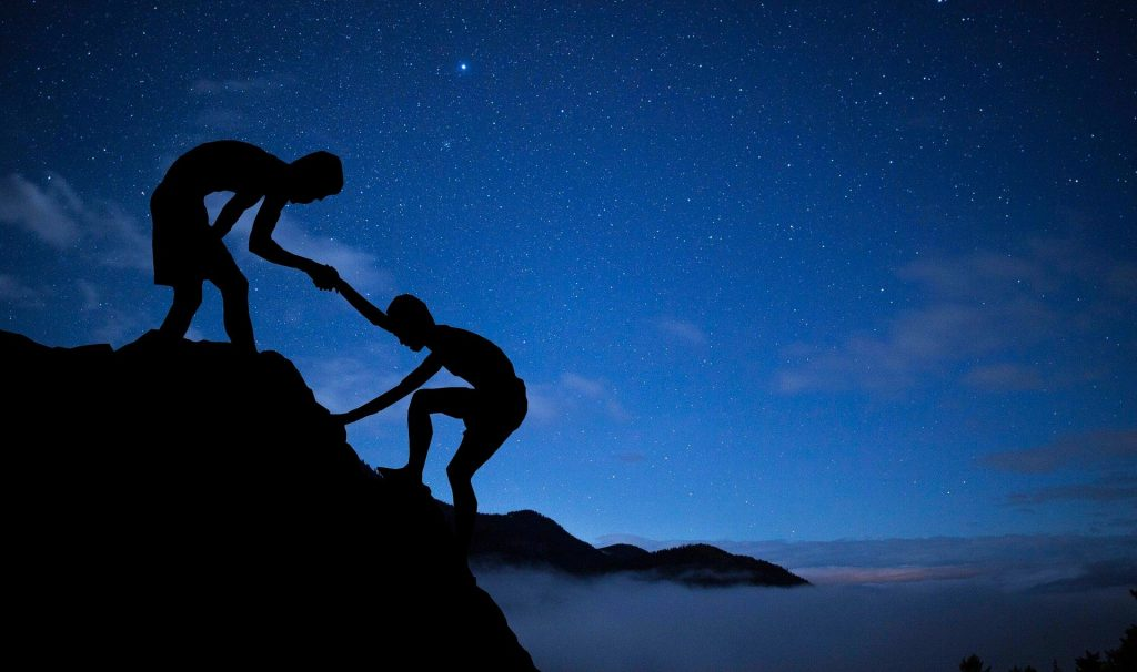 One climber helps another in a skilled ascent.