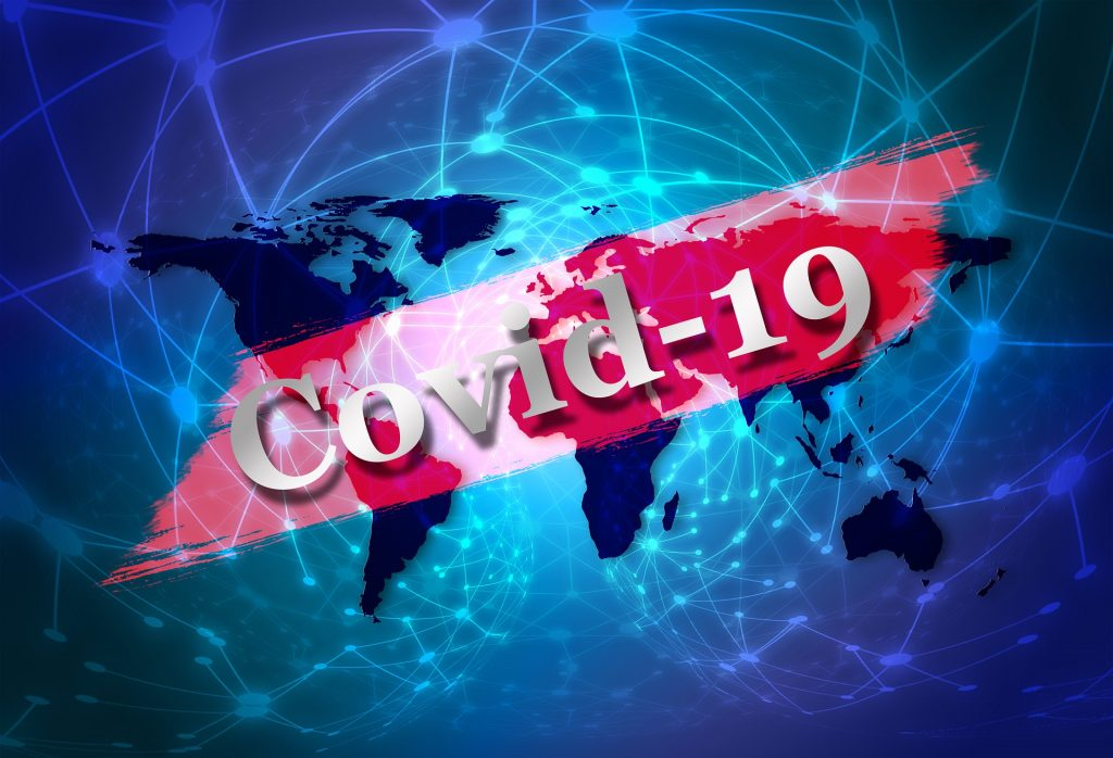 """A banner saying """"COVID-19"""" is spread across a map of the earth."""
