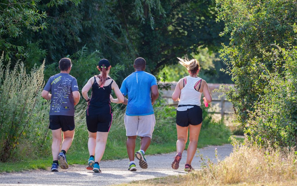 A group of runners, heavy in body, are shown running along a parklike path.